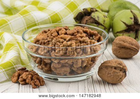Walnuts in a glass bowl on an old white wooden table. Selective focus.