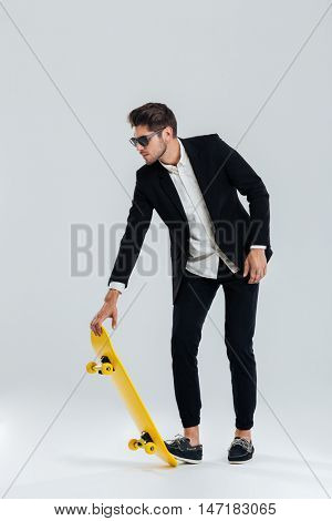 Concentrated young businessman in sunglasses and black suit going to ride a skateboard over gray background