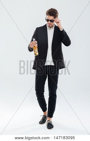 Full length portrait of a handsome serious businessman in black sunglasses holding beer bottle over gray background