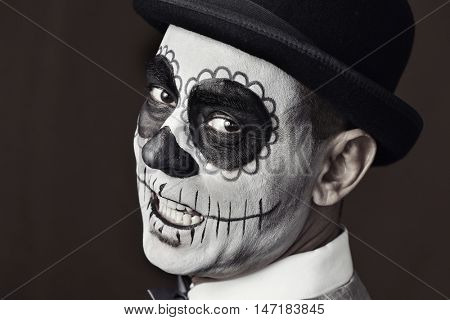 portrait of a man with a mexican calaveras makeup, wearing a bowler hat, against a dark gray background