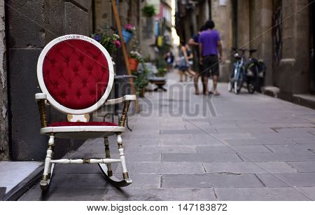 a view of a pedestrian street in the Born district, in Barcelona, Spain, with an old rocker in the foreground