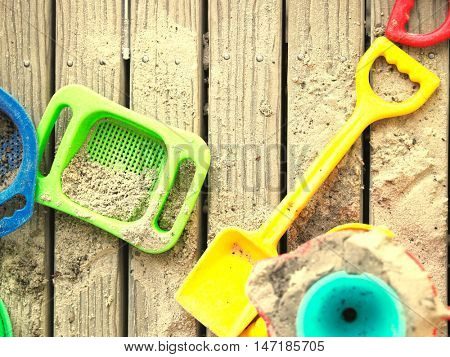 High angle view of sand pit toys lying on wooden deck