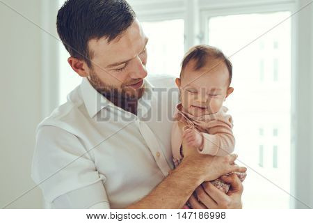 Young father holding his crying newborn baby daughter in his at home