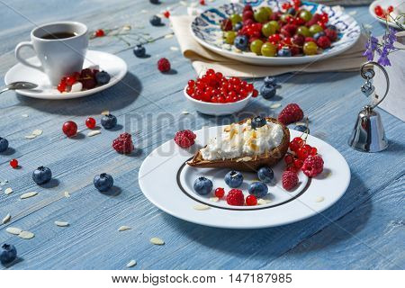 Sweet breakfast with baked pea and mascarpone dessert and berries - red currant, raspberry and bluberries. Beautiful food served at blue rustic wooden table, dish at white porcelain plate, tea cup.