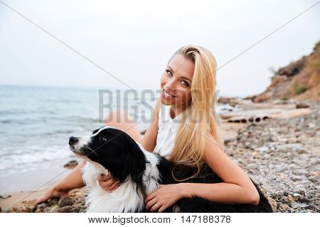 Happy beautiful young woman relaxing with her dog on the beach