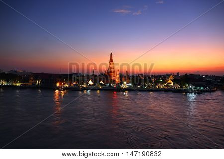 Landscape with Wat Arun at twilight time. Buddhist temple located along the Chao Phraya river in Bangkok, Thailand