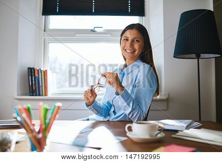 Single confident smiling woman in blue shirt holding her eyeglasses at desk in home office with bright window in background