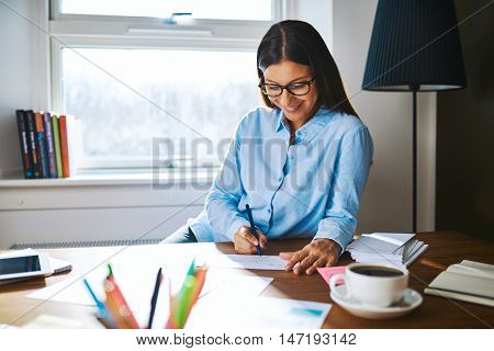 Beautiful young self-employed woman wearing glasses and blue shirt at desk writing checks next to cup of coffee and booklets