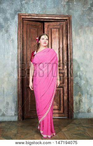 Woman in pink dress stands in room her back to wooden door.