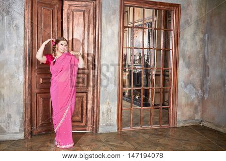 Smiling woman in pink dress stands in room with ragged walls and wooden doors.