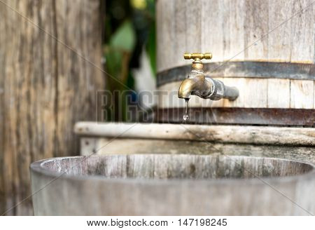 Concept saving wooden water tank with golden tap and drop of water in soft background
