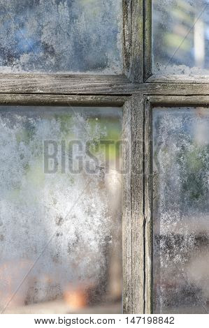 Weathered muntins and window panes on aging greenhouse