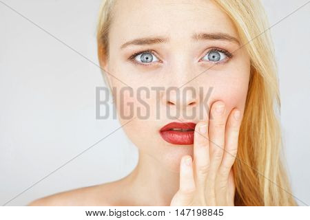 Shocked and amazed red-haired woman portrait. Attractive carroty girl touching her cheek in shock of information, free space