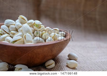 Pistachio nuts in wooden bowls placed on sackcloth background.