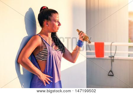 Woman biceps workout at home on terrace with sunset lights - Beautiful girl facial expression concentrated exercising arms lifting dumbbell - Concept of self body training and modern healthy lifestyle