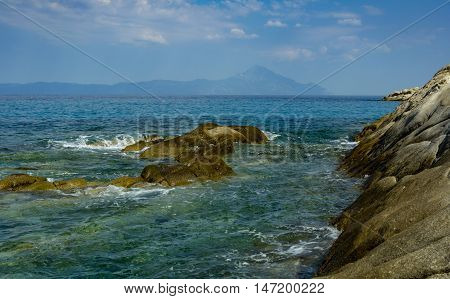 Mount Athos seen through the rocks swimming in the blue waters