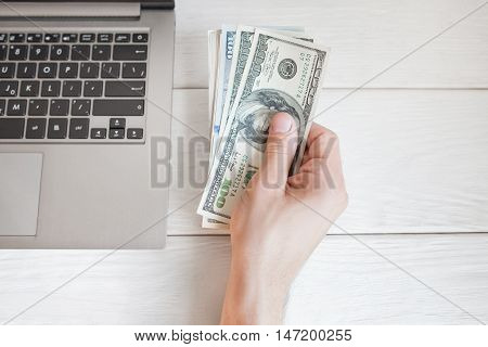 Man holding dollars near laptop, free space, flat lay. Top view on male hand with batch of american bucks near notebook, whote wooden background. Finance and earning concept