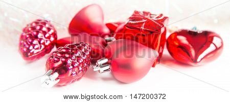 Panoramic banner with Christmas holiday decorations, red heart, pine cone, bell, gift on white background with copyspace
