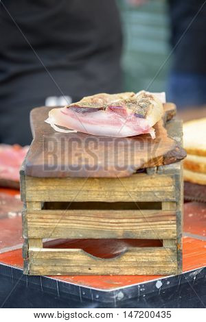 piece of speck on a cutting board on top of old wooden box