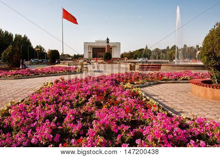 BISHKEK, KYRGYZSTAN - JULY 31, 2013: People have rest near the fountains and flowerbeds at the city main square on July 31, 2013 in Kyrgyzstan. Kyrgyzstan's popul. is 5.2 mill 34.4 perc. are under age 15