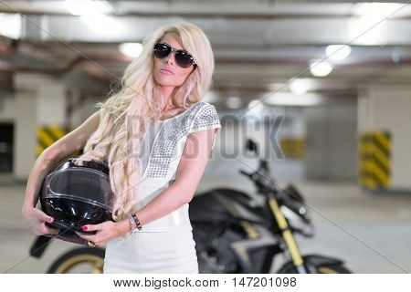 Girl with long blond hair and in white dress is holding helmet at parking lot.