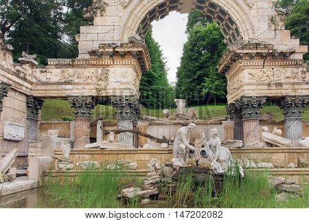 Sculpture under the ancient stone arch. Royal park near the Schonbrunn Palace, Vienna. World Heritage List of Austria