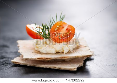 Appetizer canape with cherry tomato cheese and dill on a small loaf of bread closeup