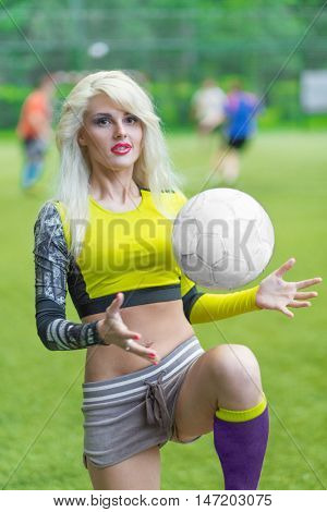 Beautiful woman plaing with ball in yellow shortened top on football field
