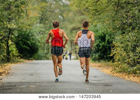 two young runners synchronous running in autumn Park. yellow leaves along road