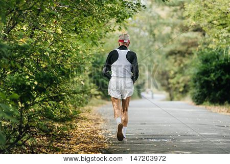back oldest male runner running in autumn Park during city marathon