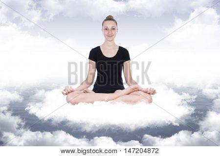 Smiling girl in yoga lotus position on the clouds that form a circle of energy around her on the bottom a blue sky with white clouds
