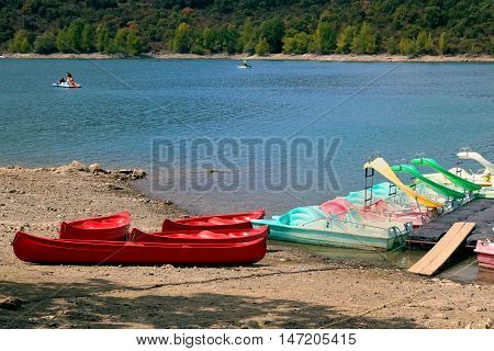 Pedalos and kayaks on the rocky shore of a freshwater lake with lakeshore trees in distance