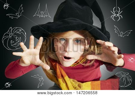 Halloween little girl looking at camera with her hand in frightening gesture