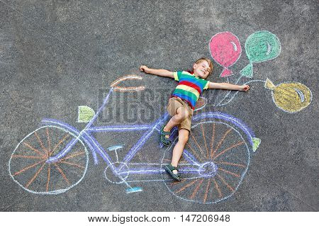 Happy little kid boy having fun with bicycle and air balloons picture drawing with colorful chalks on ground. Children, lifestyle, fun concept. funny child playing and dreaming of future and profession.