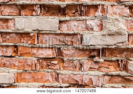 Texture old vintage crumbling brickwork with pieces of plaster