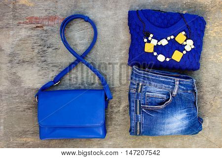 Women's autumn clothing and accessories: blue sweater, jeans, handbag, beads on wooden background. Top view.