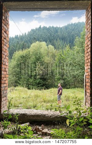 Man in shorts and a T-shirt walking in the woods. The view from the doorway of the old dilapidated brick building