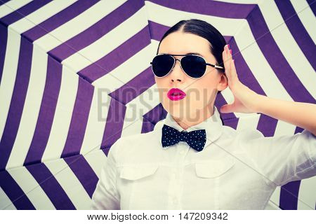 Fashion portrait of a stylish beautiful girl with sunglasses and bright painted lips next to striped background