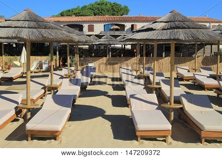 Wooden sun loungers with that umbrellas on the sand in front of a beach restaurant