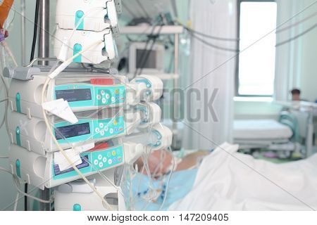 Patient in intensive care unit with modern medical devices