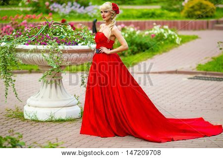 Full portrait of beautiful woman in red long dress standing in summer park around flowerpot with flowers, look at camera