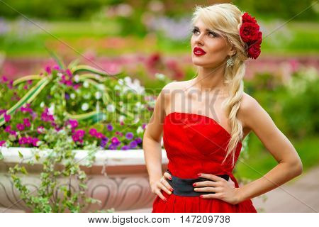 half length portrait of beautiful woman in red dress in summer park on background of flower beds, look throw