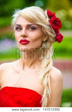 half length portrait of beautiful pretty woman in red dress in summer park, close-up