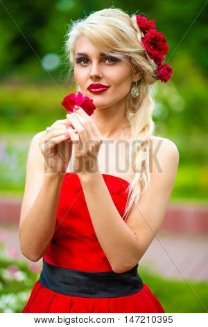 half length portrait of pretty woman in red dress smelling flower in hands in summer park
