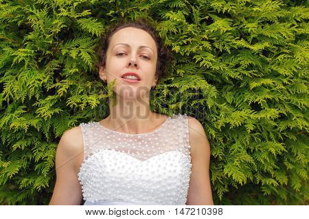 half length portrait of beautiful woman in white dress in summer park on background of green bush