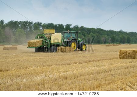 KRASNODAR REGION, RUSSIA - JUL 7, 2015: Tractor makes straw pressed bricks on yellow field after harvest, In 2015 in Krasnodar region have collected record grain harvest - 102 million tons of grain