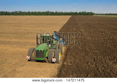 KRASNODAR REGION, RUSSIA - AUG 19, 2015: Green tractor plows field, In 2015 in Krasnodar region yields reached record level - 58.4 centners per hectare
