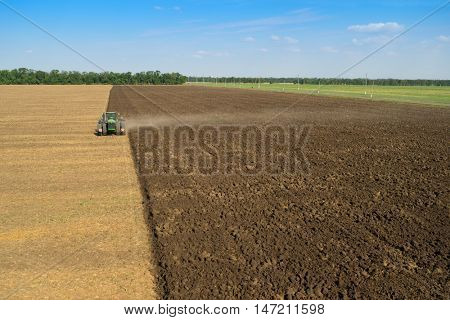 KRASNODAR REGION, RUSSIA - AUG 19, 2015: Modern tractor plows big field, In 2015 in Krasnodar region yields reached record level - 58.4 centners per hectare