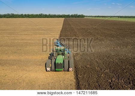 KRASNODAR REGION, RUSSIA - AUG 19, 2015: Modern tractor plows field, In 2015 in Krasnodar region yields reached record level - 58.4 centners per hectare