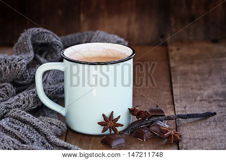 Enamel cup of hot cocoa or coffee for Christmas with chocolate bars vanilla pod spices and gray scarf against a rustic background. Shallow depth of field with selective focus on drink.